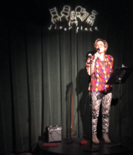 [a non binary person wearing many patterns makes sounds into a microphone, on the stage at Dixon Place, NYC.]