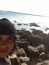 the face of a brown person in a black beanie, juxtaposed against rocks and the Pacific Ocean