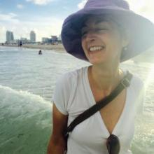 photo of Valerie Wallace on Miami's South Beach, with the skyline in the background.