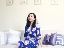 [Image Description: A queer Chinese American woman poet in a blue floral jumpsuit is sitting on a couch]