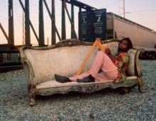 Daiquiri appears with harp on a couch near a train.