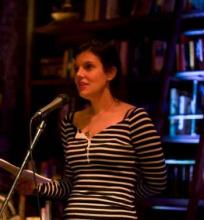 Amy McDaniel at a microphone reading her poetry