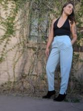 Sharon Reynolds, wearing a black top and blue slacks, standing against a vine covered wall