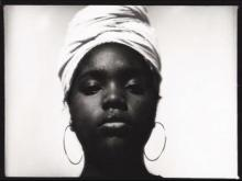 Black and white image of Akilah Toney wearing a head wrap and hoop earrings.
