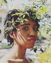 A photograph of poet Skye Jackson. She is wearing red lipstick and is standing behind a tree branch.